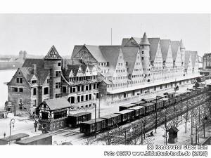 """Dieses Lagergebäude war zu Beginn des 20. Jhdt. ein technisches Novum, eines der ersten großen Gebäude, das ausschließlich aus Stahlbeton, einem damals hochmodernen Werkstoff, gefertigt wurde. In der Formensprache mit den charakteristischen Giebeln und Treppentürmen hat sich der Architekt Hans Verbeek allerdings an historische Vorbilder des 18. Jhdts. in den Niederlanden und an der Ostsee angelehnt. Das Ensemble wird daher auch """"Danziger Lagerhaus"""" genannt. Im Vordergrund die Anlagen der Hafenbahn, die zu diesem Zeitpunkt das Haupttransportmittel war, links im Hintergrund die rechtsrheinischen Flankierungstürme der Südbrücke."""